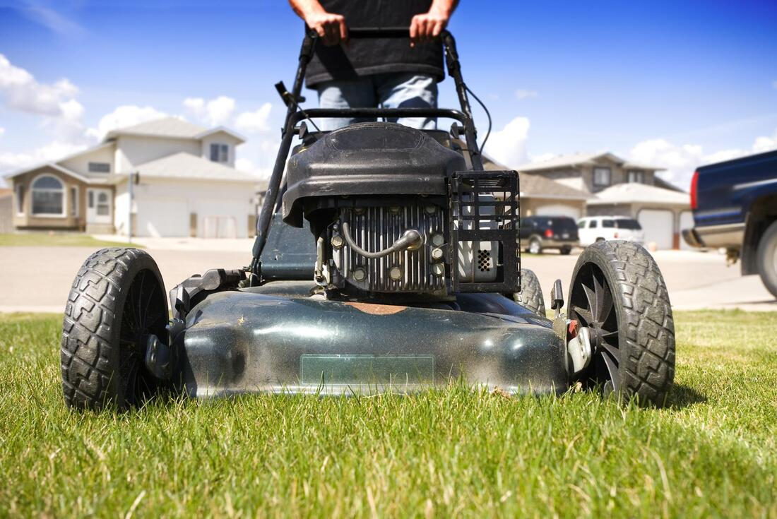 man holding a black lawn mower